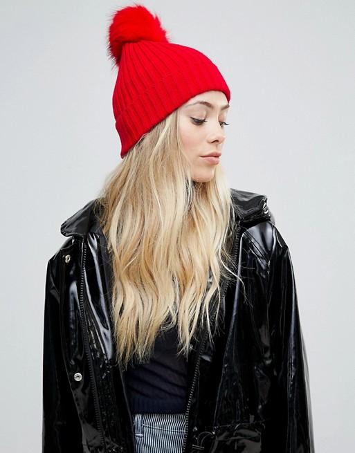 ASOS - Berretto rosso brillante a coste con pompon in pelliccia sintetica