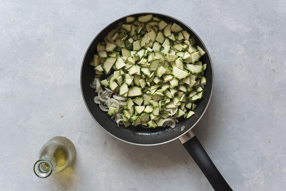 Fai saltare in padella le zucchine per la torta salata