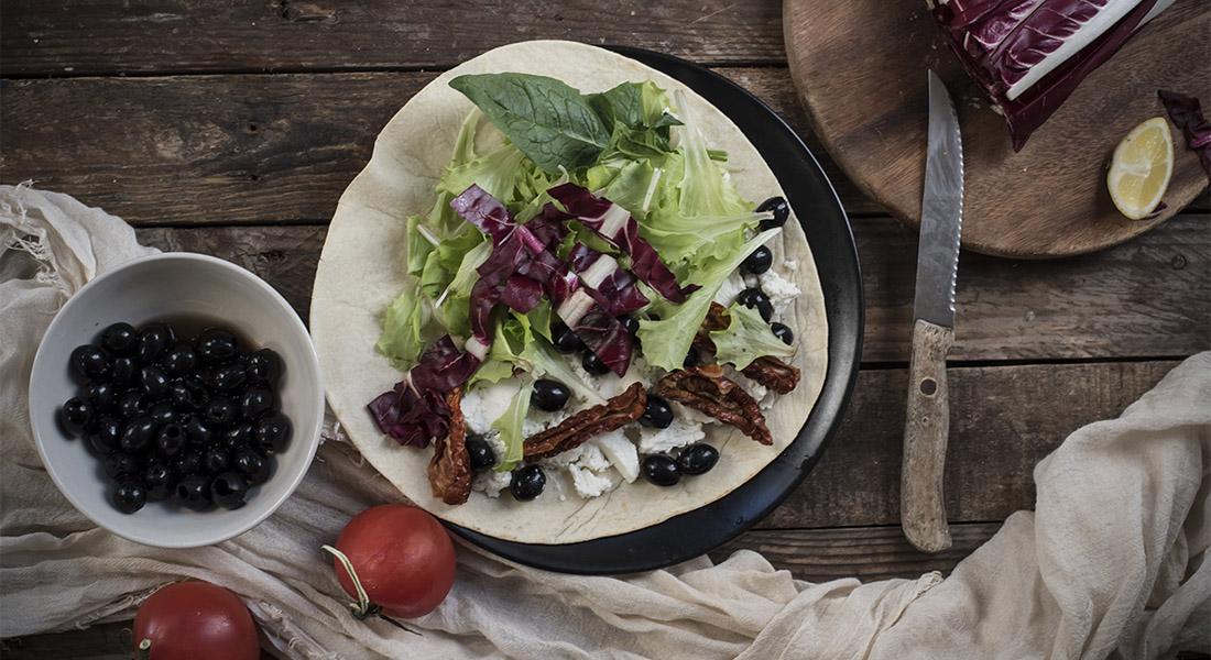 Ricetta piadina con pomodori secchi, olive, caprino e insalata