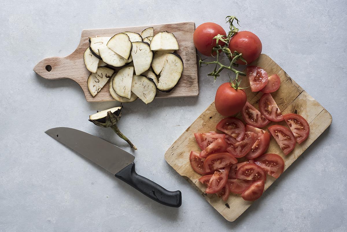 Affetta pomodori e melanzane per la torta salata di verdure