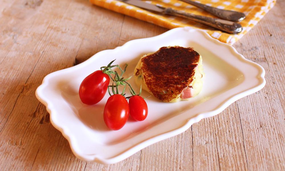 Arricchite con crescenza e prosciutto cotto, queste focaccine di patate senza glutine sono un secondo piatto sano e gustoso.