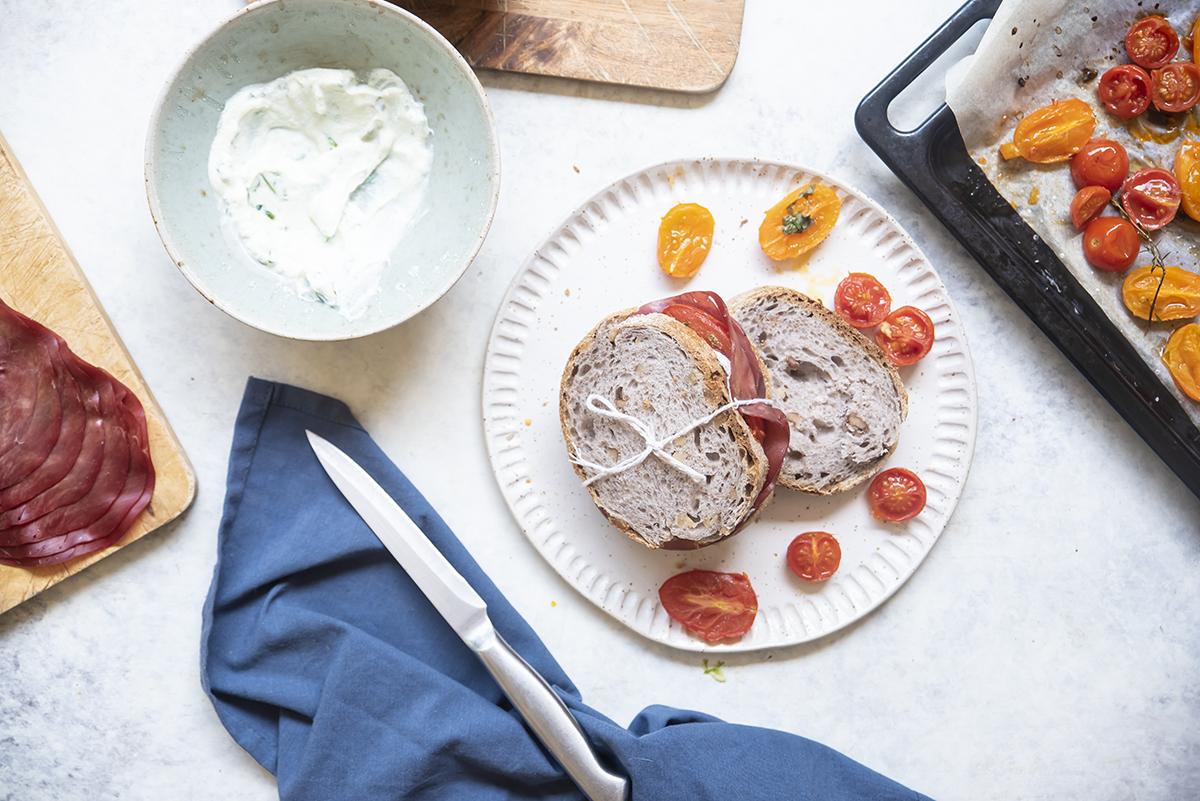Panino con bresaola, ricotta al basilico e pomodori confit