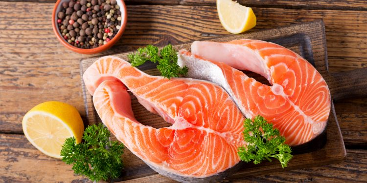 fresh salmon steaks with ingredients for cooking on a wooden table