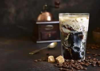 Homemade delicious iced coffee in a tall glass on a dark slate, stone or concrete background.