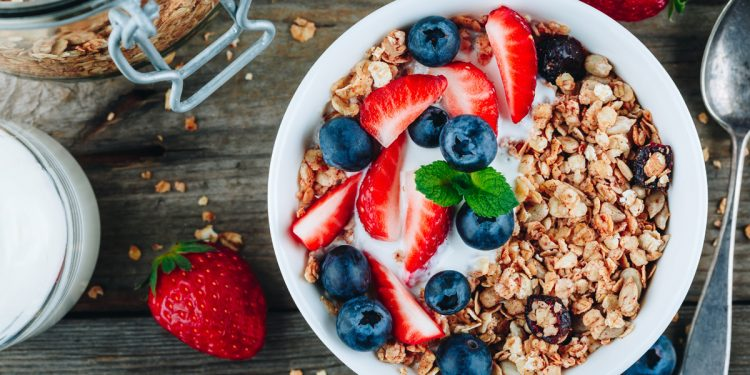 Healthy breakfast granola with fresh strawberry and blueberry on wooden background